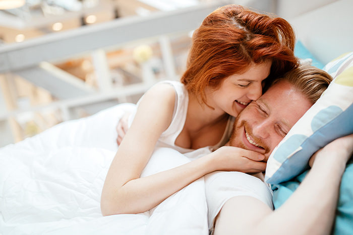 Couple in love hugging kissing in bed