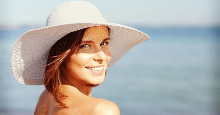 En kvinna i hatt solar sig på stranden. Under sommarhalvåret får vi D-vitamin från solen.
