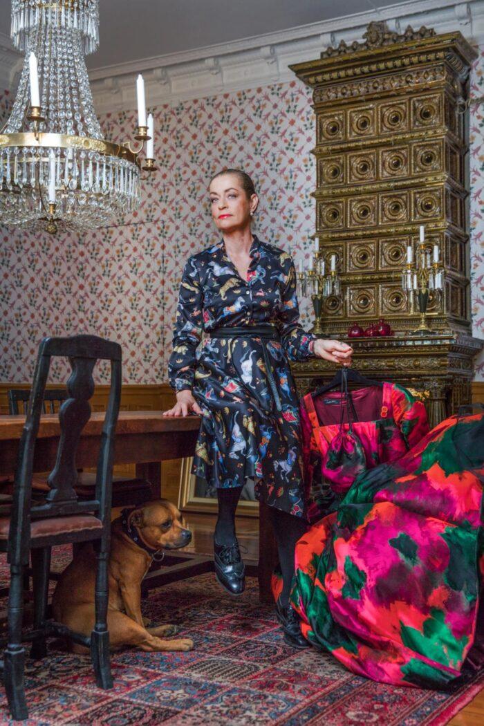 53d47b8f Camilla Thulin sitter på ett bord och håller i en klänning med hunden Musse  under bordet