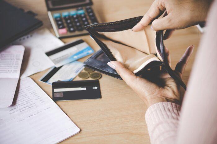 Kvinna som håller upp tom plånbok framför dator
