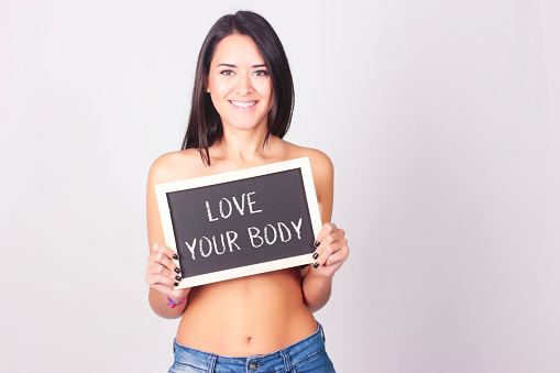 Young woman with chalkboard that says Love Your Body