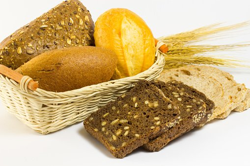 Different kinds of bread in a wicker basket. Wheat spikelets